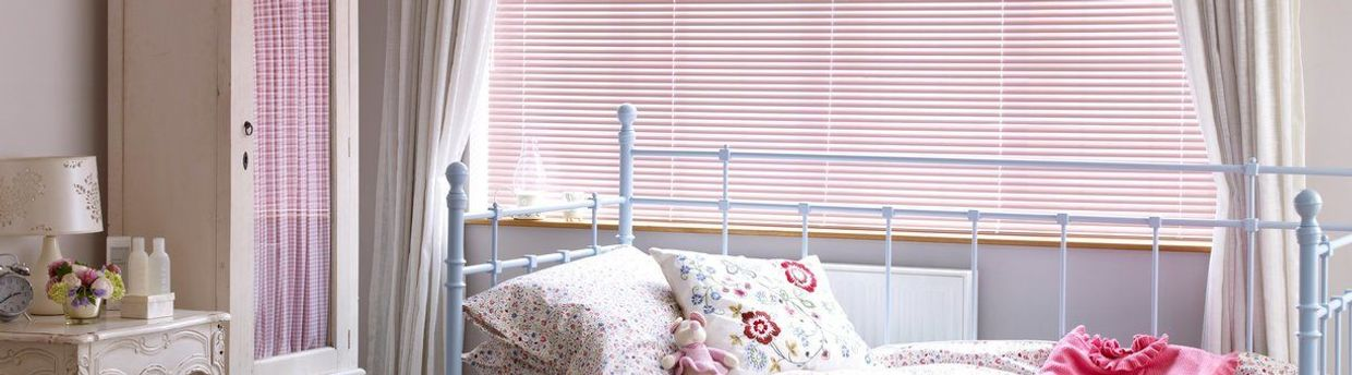 Pink venetian blinds in a bedroom