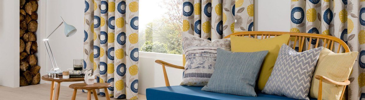 Scandi themed living room, wooden sofa with deep blue and yellow pillows and cushions and matching blue and yellow curtains in Natur Freyja Mustard fabric.