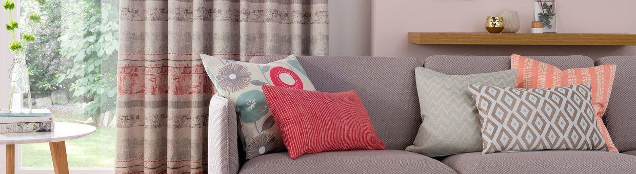 Minimalistic living room with a light grey sofa and pink cushions and matching pink curtains in Natur Fjord Coral hung in the window.