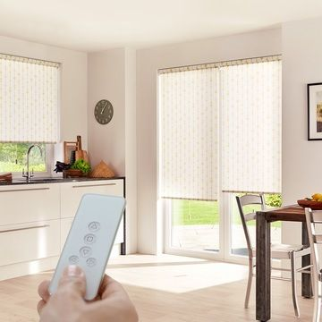 Someone operating a Motorised Roller Blind in Retta Gold with a remote control