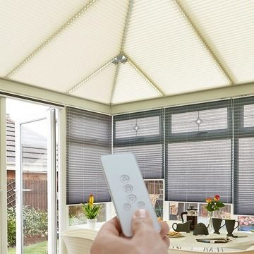 Someone operating a Motorised Roof Blind in Elba Ivory with a remote control
