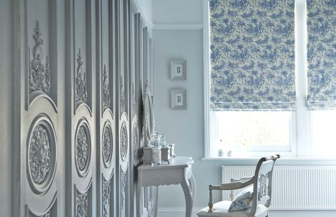 Large white room with ornate wooden panels on the walls and two Roman blinds fitted to the windows in Toile French Blue fabric