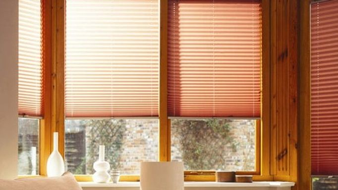 orange pleated blinds in wooden windows