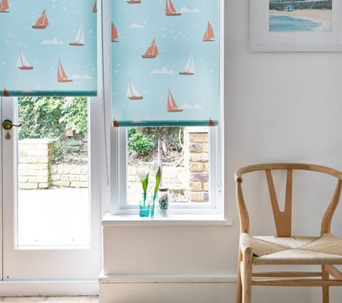 Boats Teal Roller Blind in room with white walls and wooden chair