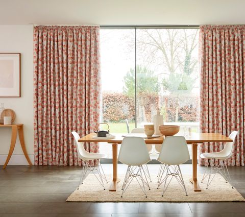 Dining Room with wooden table and large window dressed with Honesty Persimmon Printed Pink Curtains