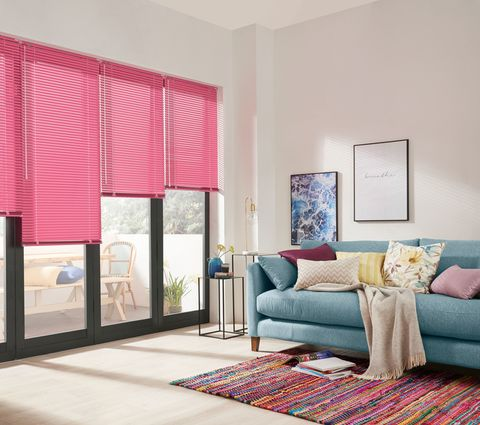 Fuschia Venetian Blind on a bifold door in a modern living room with a sofa, cushions and rug