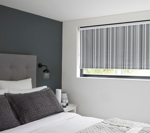 Lester Silver Roller blind hanging in a bedroom