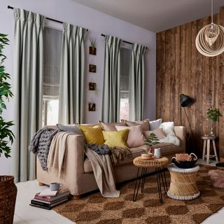 Rustic, cosy Living Room with two windows dressed with Lindora Silver Curtains and Howard Chartreuse Roman Blinds behind a sofa with cushions and blankets