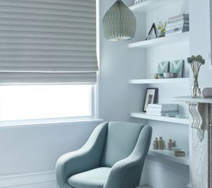 Roller Blind in Lazio Natural in a Bedroom with blue armchair and bookcase