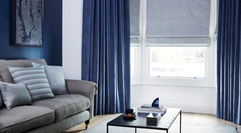 Cosy living space with grey sofa and window dressed with blue velvet curtains
