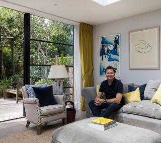 George Clarke sat on a couch in front of floor to ceiling Crittall windows