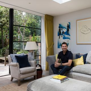George Clarke sat on a couch in front of floor to ceiling Crittall windows with yellow curtains