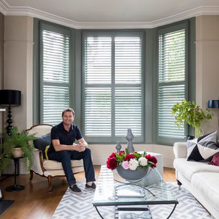 George Clarke sat in a Living Room with Full Height Shutters in a Bay Window