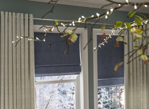 Festive room with Beige Eyelet Curtains in Malva Duck Egg Fabric paired with Islita Blue Roman Blinds