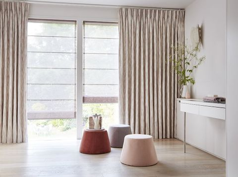 Minimalist room with sliding doors dressed in full length curtains and Voile Roman blinds