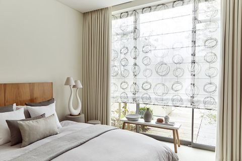 Bedroom with minimalist decor and curtains layered over Voile Roman blinds