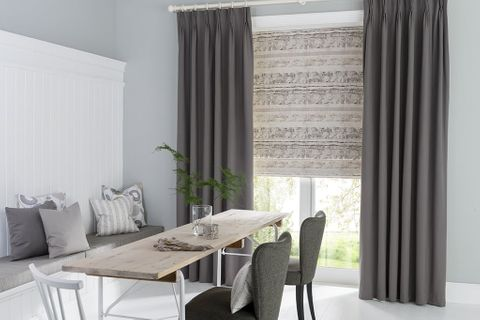 Minimalist Dining Room with Dark Grey Pinch Pleat Curtains in Tetbury Charcoal fabric layered with a roller blind