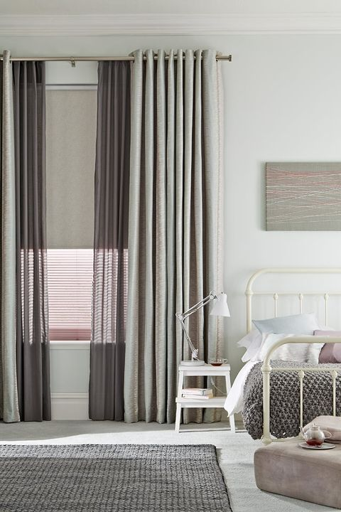 A cosy bedroom with layered Window Furnishings with Pink Pleated Blinds, Grey Roller Blind, Light Grey Voile Curtain and Blue Mist Curtains