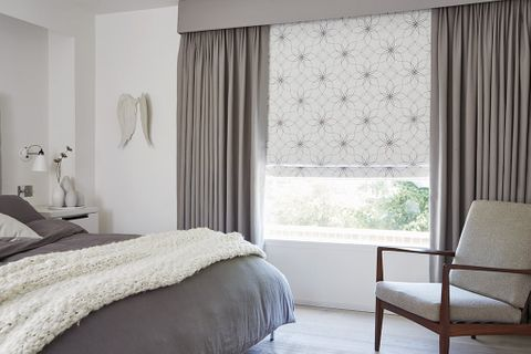Cosy Bedroom with Blackout Curtains in Tetbury Charcoal fabric layered over white pattern Roman Blinds in Lavida Smoke fabric