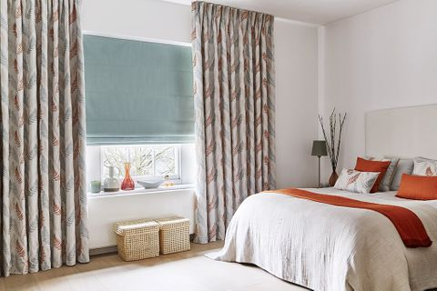 Neutral Bedroom with patterned Pinch Pleat Curtains in an orange and blue pattern