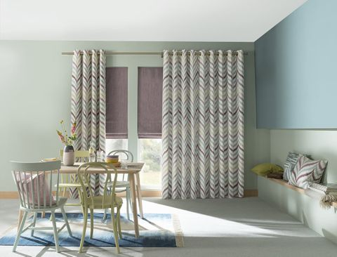 Dining Room with Pattern Eyelet Curtains in Souk Berry Haze Fabric layered over Islita Thistle Roman Blinds