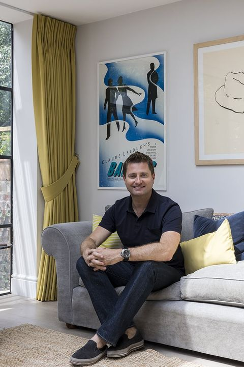 George Clarke sat in a living room with yellow curtains tied back