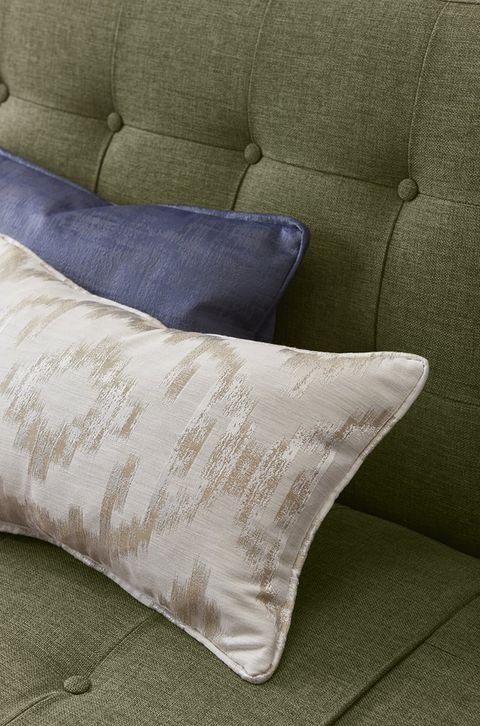 Green sofa with cushions in blue and beige fabric to match living room curtains