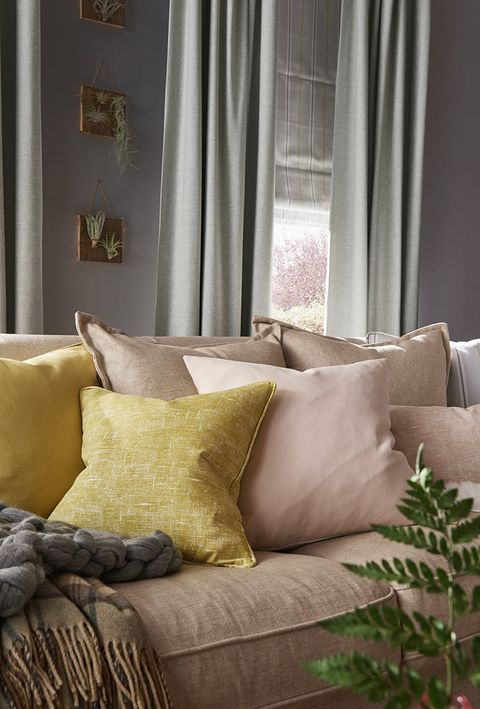 Cosy Living Room Sofa with Cushions and Blankets in front of a window dressed with Grey Curtains