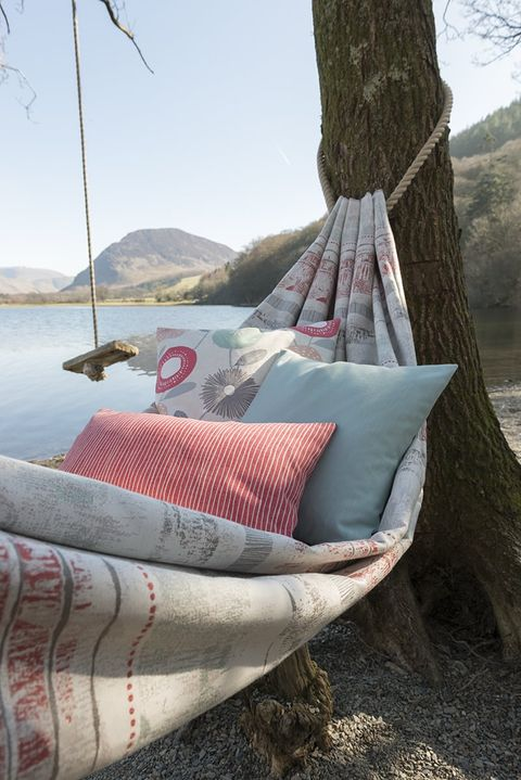 Hammock strung between two tress made with pink fabric and matching cushions