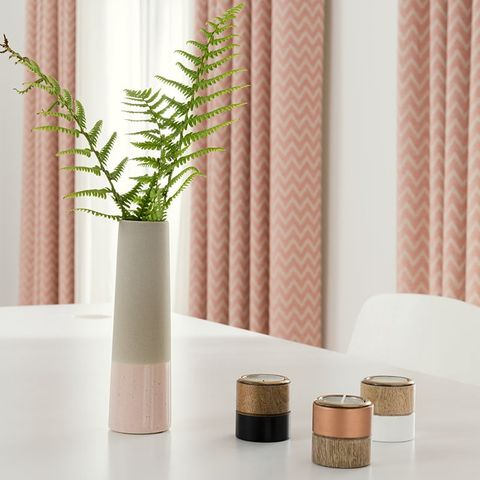Dining table with a plant and patterned pink curtains