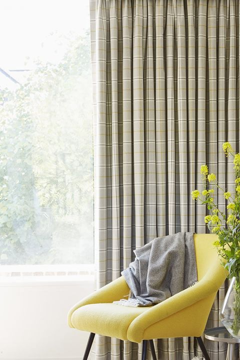 Bright yellow armchair in front of patterned cream curtains