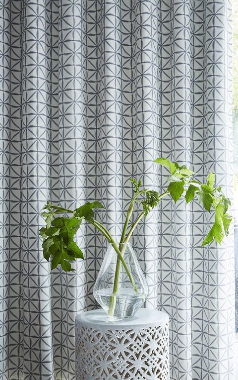 Side Table with a Clear Vase with lucky bamboo in front of a Patterned White Curtain in Shibori Smoke fabric