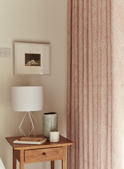 Bedside table next to full length pink curtains