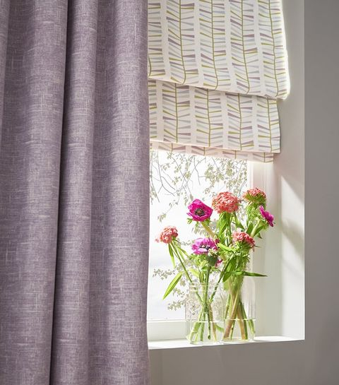 Close up of a Window dressed with Purple Curtains in Emelie Heather Fabric and a vase of flowers on the window sill