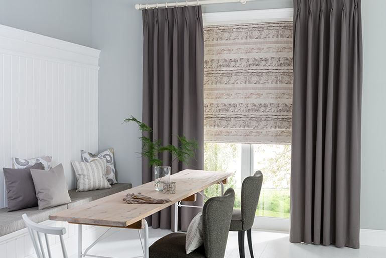 Dining room with table and bench and patio doors with plain grey curtains