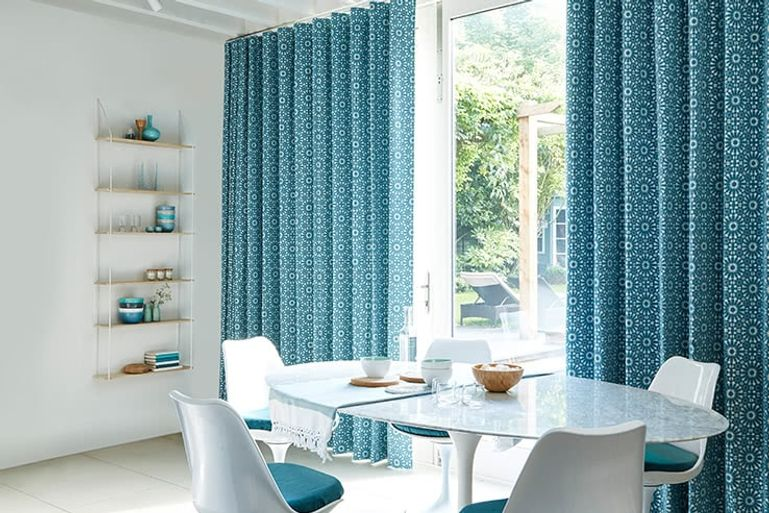 White minimalist dining room with patio doors to the garden dressed with bright blue curtains