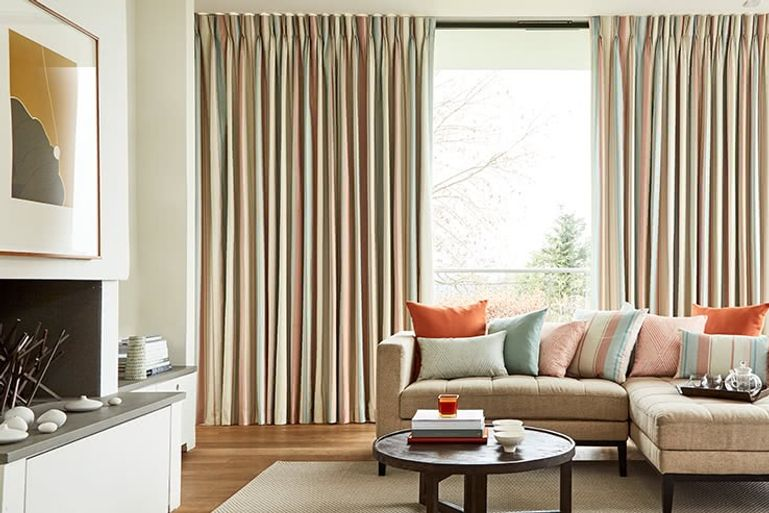 Living with wide windows dressed with full length cream curtains with pastel tones