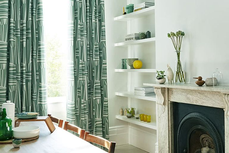 Bright dining room with feature fireplace and patterned green curtains