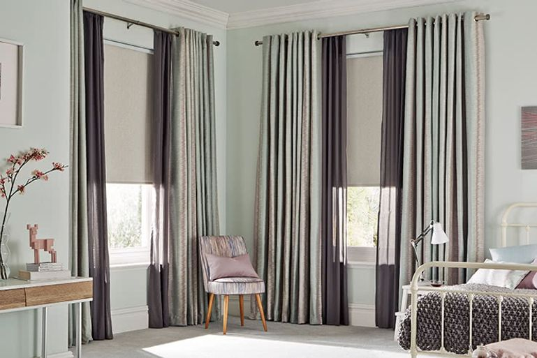 Bedroom with double aspect windows dressed with full length grey curtains layered with matching grey voiles