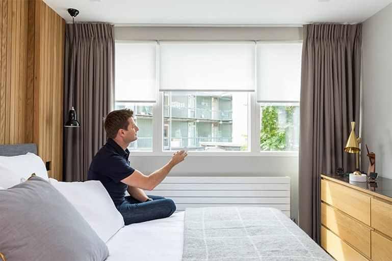 George Clarke operating motorised grey curtains in a bedroom