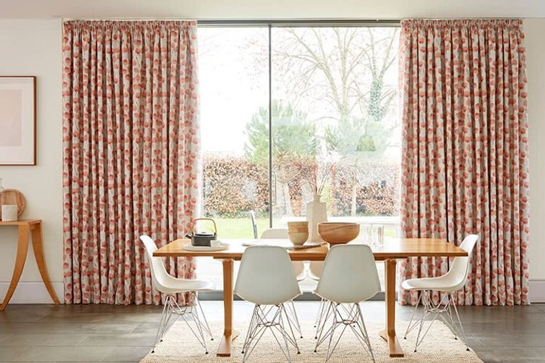 Open plan kitchen diner with patio doors dressed with coral orange curtains