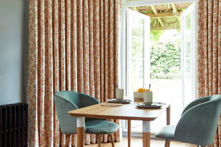 Dining room with small wooden table and patio doors to the garden dressed with patterned orange curtains