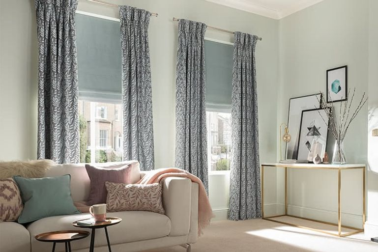 Grey curtains paired with duck egg blue roman blinds fitted to tall rectangular windows in a living room decorated in neutral tones while also featuring a sofa and coffee table