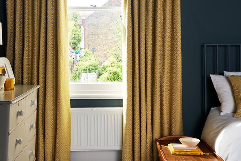Bedroom with dark walls contrasting with patterned yellow curtains