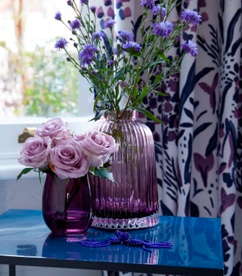 Purple glass vase placed on table in front of a window dressed with white and purple printed curtains
