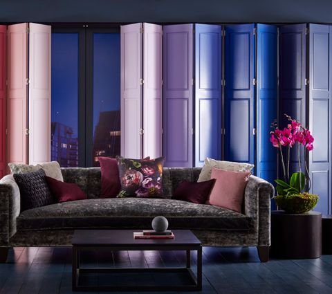 pink, blue and purple range of coloured shutters in a living room window at night time