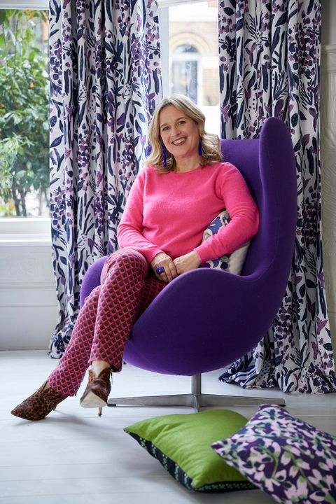 Sophie Robinson sat on a Purple Chair with matching colour curtains and cushions