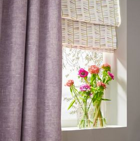 Purple shimmering curtains over cream printed roman blinds hanging on window