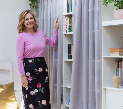 Liz Earle in a home office with soft grey voile curtains covering a bookcase with books and plants