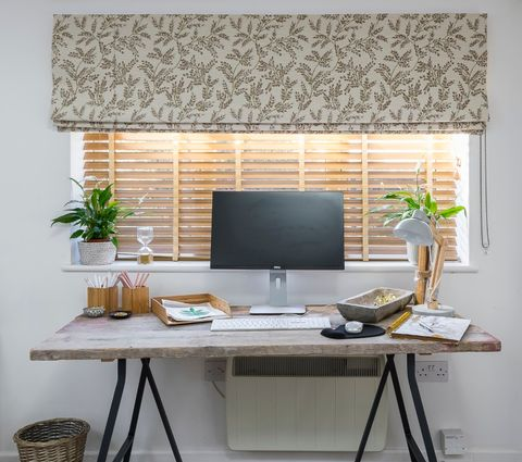 Liz Earle's home office with oakwood faux wooden blinds behind a small desk and computer